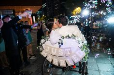 PediCab exit from the Mint Museum Uptown wedding with bubbles / Wedding Design: The Graceful Host / Centerpieces: New Creations Flower Company / Photography: Jeremy Igo Photography / Venue: Mint Museum Uptown Atrium / Wedding Dress: Vera Wang from Nitsa's Apparel / Charlotte, North Carolina Wedding