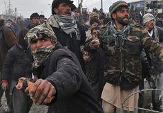 La juventud afgana a lanzar piedras hacia los soldados estadounidenses de pie en la puerta de la base aérea de Bagram, 21 de febrero de 2012. Manifestantes afganos disparando hondas y cócteles molotov sitiada una de las mayores administrados por Estados Unidos bases militares en Afganistán, furiosos por los informes que la OTAN había prendido fuego a las copias del Corán. (Massoud Hosssaini / AFP / Getty Images) #