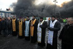 Priests of different faiths pray at protests during clashes with police in central Kiev. (Sergei Chuzavkov/AP)