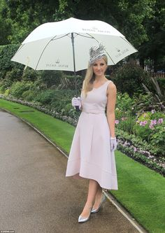 One spectator defies the rain to make a stylish entrance at a very wet and rainy Ascot Races. 14 June 2016.