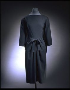 Dress | Cristóbal Balenciaga | V&A Search the Collections: This is a sack dress by Balenciaga. This dress was made in Spain in 1957. It is made of wool. It has a slim semi-fitted outline with a round neck, elbow length sleeves, and a belt.