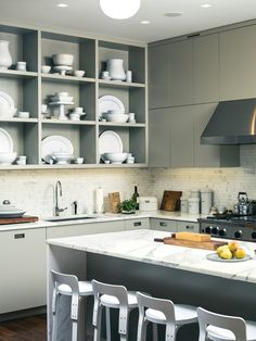 """Custom kitchen cabinets designed by Pulltab and fabricated by Maciek Winiarczyk hold mostly vintage ironstone that Geiger has found at flea markets and estate sales over the past 20 years. """"I love white,"""" she says, """"because I think food always looks better on it."""" She also collects vintage wooden cutting boards, shown resting against the marble tile backsplash from Stone Source."""