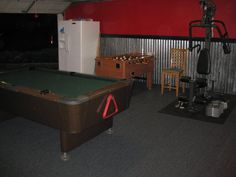 The man cave is stocked with the necessities: a vintage '57 Valley Pool Table, a foosball table, exercise equipment & a fridge.