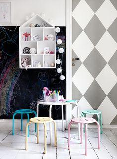 Paper on door, house shelves, pastel stools,  blackboard wall