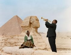 Louis Armstrong plays for his wife, Lucille, in front of the Sphinx and Great pyramids in Giza, Egypt, 1961