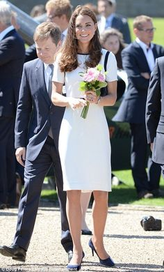 Meet and greet: A smiling Duchess of Cambridge was handed a posy of pink flowers as she toured the museum