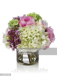 A small spring bouquet of mixed flowers in a round glass vase. It contains hydrangeas, peonies and other flowers. Shot against a bright white background. There is a path which may be used to delete...