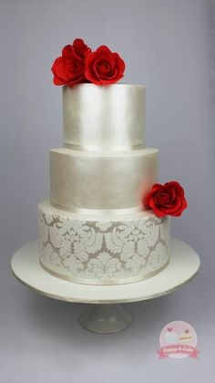Satin and damask wedding cake ~   covered in shimmer, with lace stencilling and topped with red  sugar roses