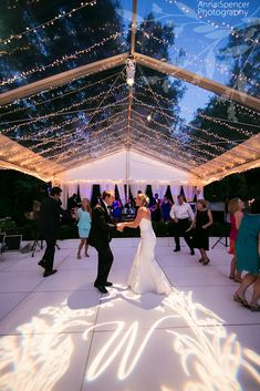 Buckhead Atlanta Documentary Wedding Photographers, Anna and Spencer Photography. Bride and groom dancing on a white dance floor, under a clear tent with christmas lights and a monogram gobo.