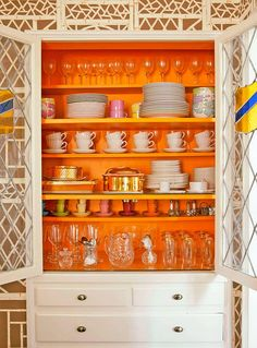 A cream-colored hutch with tangerine interior makes a stunning impression, highlighting the homeowner's collection of retro dishware - Traditional Home®  Photo: John Ellis Design: Carmen Lopez