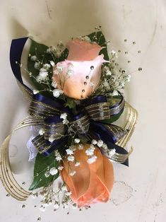 Peach roses, baby's breaths, and green leaves with navy and gold trim on a wristlet. Wrist Corsage, Corsages, Boutonnieres, Sprays, Green Leaves, Roses, Peach, Table Decorations, Navy