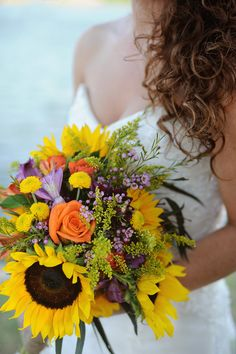 Bouquet with sunflowers, orange roses, and purple and green accents.  Photography by twotimesphotography.com