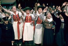 Young German girls sporting traditional Volk dress as it displays a Harkening to the past, toward better times in remembrance to older days where the mighty German lands were pure and majestic. And the sheer willpower and effort one must muster in order to achieve the noble task of bettering the livelihood of ones own heritage.  These showwomen congregate together closer to the street side so they may snap a photo of the Führer of the German Reich as he passes by on his motorcade.