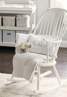 Witte schommelstoel op schapenvacht
