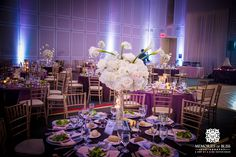 This purple, gold and white décor has a classic yet fun look. Gold chivari chairs are included in all of our wedding packages. Elegant wedding table.  #tablescape #centerpiece