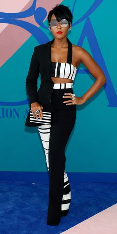 Janelle Monae never fails to stun with her whimsically modern looks. At the Council of Fashion Designers of America Awards where she delivered an impassioned speech, the actress-musician wore an asymmetrical suit jacket-crop top hybrid with matching black and white striped trousers. She accessorized the winning look with a hardcase Edie Parker clutch, an assortment of glimmering rings, and a pair of mirrored sunglasses.