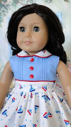 1950's Inspired dress for American Girl doll. Cyria based this little sleeveless dress based on the photo of an actual 50's dress. She used a darling sailboat motif cotton print for the skirt, and solid blue for the bodice. The bodice is fully lined, has little tucks on the front flanking both sides of 3 decorative cherry red buttons down the front. Cherry red piping edges the bodice where it meets the skirt and around the sweet, white rounded collar.