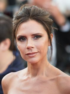 Victoria Beckham wears a simple updo with a few loose pieces of hair framing her face and bare shoulders at the Cannes Film Festival 2016.