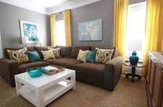 brown, gray, teal and yellow living room with sectional sofa and white coffee…