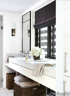 """The challenge in the master bathroom was using every available inch of space,"" says Booth, who under-mounted twin Kathryn sinks from Kohler. The faucets are from Kallista and the custom mirrors are by McAlpine."