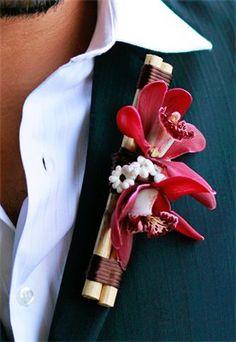 Boutonniere made of mini red cymbidium orchids, seashells and bamboo