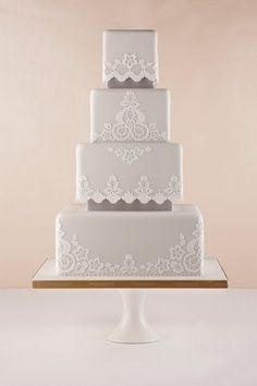 An impressive yet demure wedding cake in pale grey with white lace-like accents.