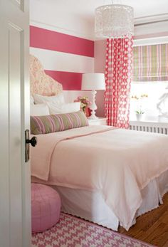 Pink-striped wall, pink drapes, pouf, & carpet bedroom