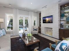 """A light and airy living room. The """"fireplace"""" is filled with candles for an interesting decor choice."""