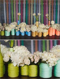love this centerpiece of yarn wrapped mason jar and wine bottle vases (via rainbow wedding ideas)