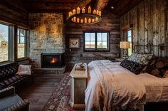 rustic bedroom featuring a fireplace with a beautiful stone surround and hardwood flooring located in Woodland, Utah. (via Magleby Construction)