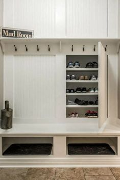 Custom mudroom storage with concealed shoe storage, 8 hooks for coats and two large cubbies.