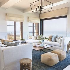 A beach living room in navy, blues and tan, with upholstered furniture, leather ottomans, tan Roman shades and printed pillows. Beach Living Room, Coastal Living Rooms, Home Living Room, Living Room Decor, Living Room Lighting, Dining Room, Beach Cottage Style, Beach Cottage Decor, Coastal Decor