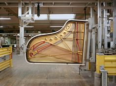 "Inside the Steinway Factory - Photographs - NYTimes.com.   ""A machine turns the piano on its side so its legs can be easily attached."""