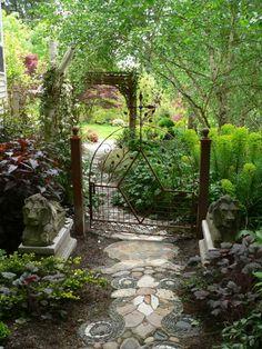 Magnifique portail de jardin, en arrière-plan une arche métallique paraissant tissée. //  Beautiful small garden gate; in the background, a metallic arch that seems to be woven.