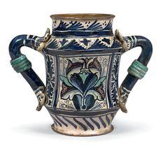 MONTELUPO ou DERUTA Circa 1460-1470 Albarello légèrement cintré muni de deux anses à fond bleu terminées par des pétales stylisées et ornées au centre d'un bandeau annelé décoré en bleu, vert et violet… - Beaussant Lefèvre - 31/01/2017