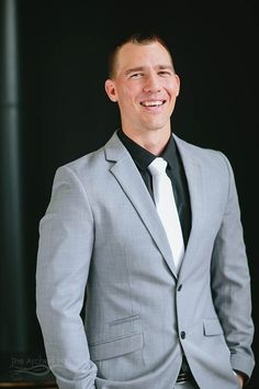 groom grey suit black shirt and white tie on wedding day