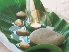 palm frond boat with bananna leaves, stones, jasmine flowers, and teacandle.
