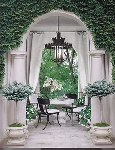 .This little balcony / porch is beautiful. The Ivy on the walls, the large urns / planters, the pillars ...ahh...