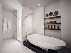A masterclass in combining materials in a bathroom design. Here, white Calacatta Gold marble slabs are combined with a black marble plinth. A simple solid surface bath and warm wooden shelves round out the look. Bad Inspiration, Bathroom Inspiration, Bathroom Layout, Small Bathroom, Bathroom Ideas, Bathtub Ideas, Bathroom Designs, Bathtub Shower, Bath Tubs