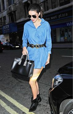 Kendall Jenner wears a belted denim dress with ankle boots and a leather satchel