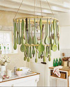 Un lustre avec une structure en bambou qui accueille des ustensiles de cuisine en bois peint en vert