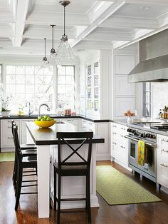 Wood floor, white cabinets, black counters.