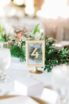 gold framed table numbers - photo by Elaine K Garland Photography http://ruffledblog.com/gold-and-greenery-garden-wedding