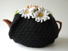 Knitted tea cosy in wool with lining and daisy decoration