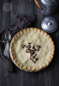Great idea! Get a stencil and use dark vegetable juice (like beets or whatever ingredient is in your pie) to imprint a design.  Hipster bakers everywhere are now rejoicing ;)