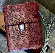 Hand tooled leather journal with stunning stone inlay and leather tie. Inside contains 200 pages of off white, unlined paper. 8in x 6in. Choose your stone color when ordering.