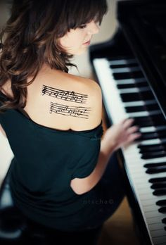 Musical tattoo on back shoulder.