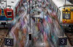 A intensa movimentação de pessoas preenche praticamente todos os espaços nessa plataforma de embarque em uma estação de trem de Mumbai, Índia.