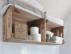 etagere cagette dans la salle de bains, rangement serviettes blanches, rouleaux de papier toieltte, panier tressé, bouquet de fleurs