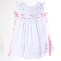 White Smocked Geometric Dress with Pink Satin Bows - White geometric smocking compliments the pink flowers on the adorable Easter dress. Pink Satin Ribbons on the side. Perfect for your little girl this Easter.